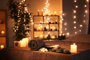 Massage stones with towel and candles on table in spa salon