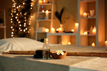 Massage stones and essential oil on table in spa salon