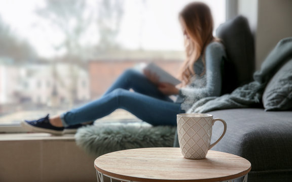 Cup on table of young woman reading book on window sill