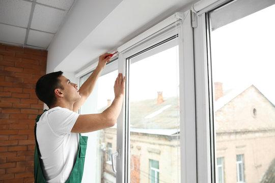 Young worker repairing window in flat