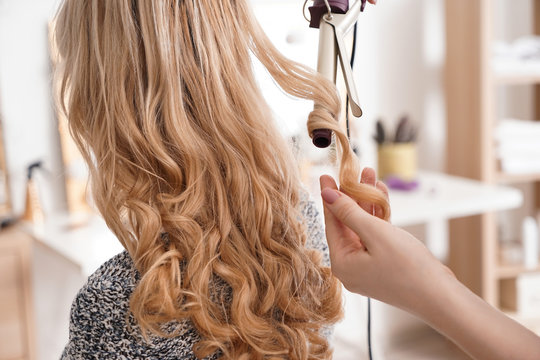Hairdresser curling long hair of young woman in salon