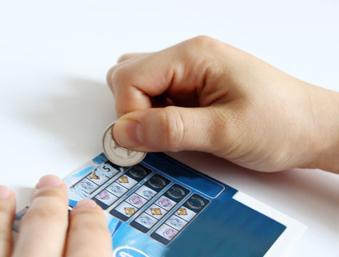 A woman's hand scratching an instant lottery ticket with a coin.