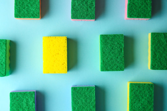Yellow sponge among green ones on color background. Concept of uniqueness