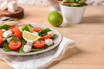Healthy salad with feta cheese on wooden table