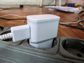 White USB charging for gadgets on a blurred background of the room, close-up. The concept of technology in everyday life, the image with the effect of shallow depth of field with copy space