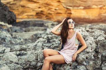 Wall Murals Old abandoned buildings Pretty long hair brunette tourist girl relaxing on the stones near sea.