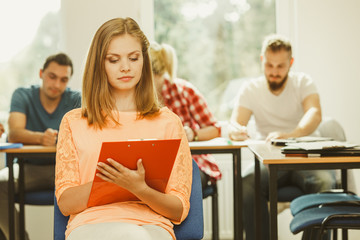 Student girl in front of her mates in classroom