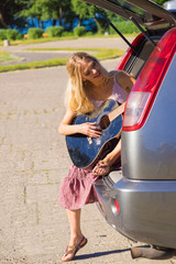 Hippie woman playing guitar in van car