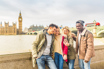 Happy multiracial friends group using smartphone in London
