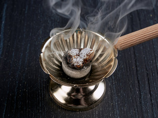 Burning incense in a simple Romanian orthodox censer or incense burner