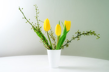 spring bouquet, vase with yellow tulips and branches on a white table against a blue gray background with copy space