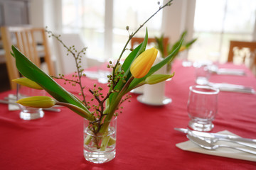 bouquet of yellow tulips on a casual set table with red tablecloth
