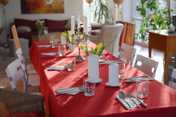 improvised dining table for many guests with red tablecloth and decoration in the living room