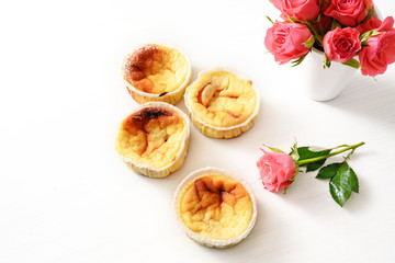 homemade small curd cakes or muffins and pink roses on a white table with copy space, background fades to white