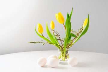 Easter bouquet with yellow tulips and spring branches in al glass an four eggs on a white table against a gray background with copy space