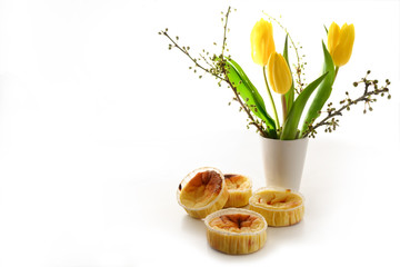 homemade small cheese cakes or muffins and a vase with yellow tulips on a white background, copy space