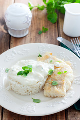 Fried cod, cooked with rice and cream sauce on a white plate, selective focus