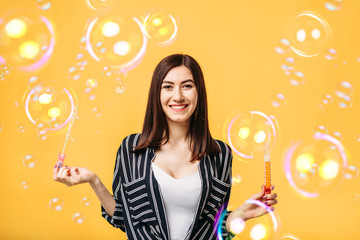 Young woman blows soap bubble, yellow background