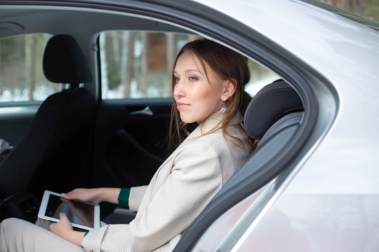 Attractive executive female manager working with a tablet in a backseat of a car