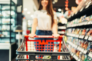 Female customer with cart in food store