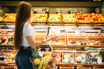 Female customer against fruit section in food store