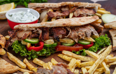 Gyros, shawarma, take away, street food.  Sandwich with meat on wooden table