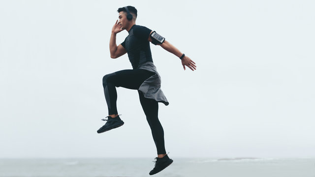 Sporty man exercising jump and lunge