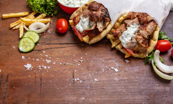 Gyro pita, shawarma, take away, street food. Traditional greek turkish, meat food on wooden table