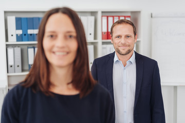 Businessman posing in the office with a colleague