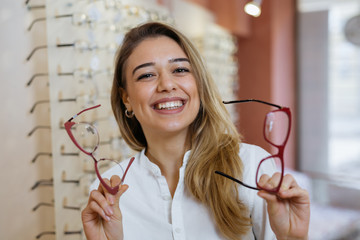 woman choosing eyeglasses in optic store Wall mural