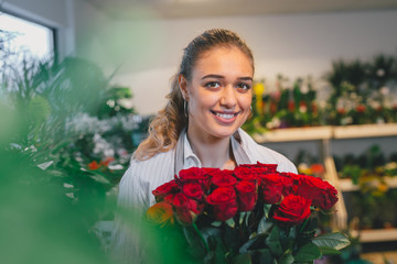 florist holding bouquet of roses in flower shop