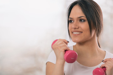 portrait of young woman holding pink weights, looking away