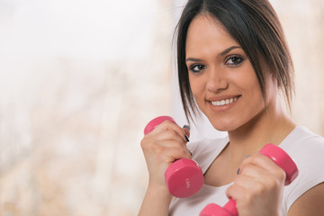 closeup portrait of young woman holding pink weights