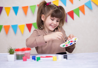 Child making homemade greeting card. Little girl paints heart on homemade greeting card as gift for Mother Day. Traditional play concept. Arts concept