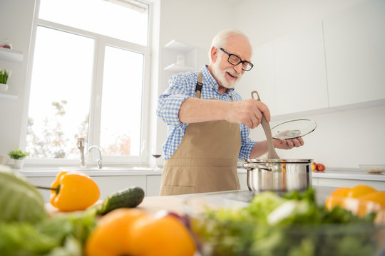 Close up photo grey haired he his him grandpa appetite waiting guests cooking favorite family dish mix all in pan ready wear specs casual checkered plaid shirt jeans denim outfit kitchen indoors