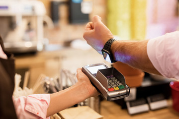 Person paying at cafe with smart watch wirelessly on POS terminal