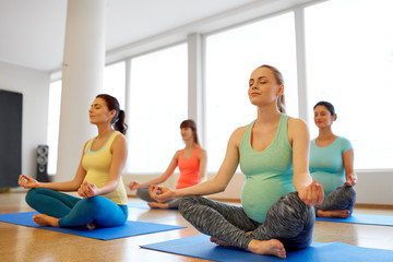 pregnancy, fitness, people and healthy lifestyle concept - group of happy pregnant women meditating in lotus pose at gym yoga