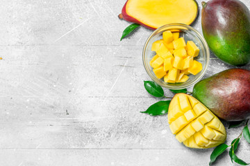 Mango slices in a bowl and fresh mango with leaves.