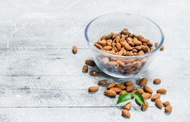 Almonds in a glass bowl with leaves .