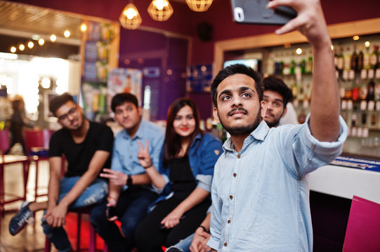 Group of stylish asian friends wear on jeans sitting at chairs against bar in club and makes selfie together.