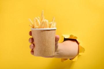 Hand giving French fries