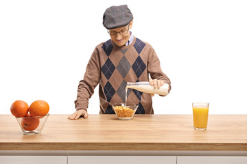 Senior man pouring milk into a bowl of cereals on a wooden counter