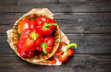 Ripe red sweet peppers in a basket on paper.