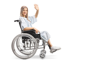 Smiling female patient in a wheelchair waving at the camera