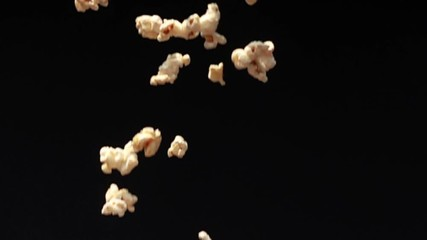 Fototapete - Popcorn fall down to the ground on black background in Slow Motion
