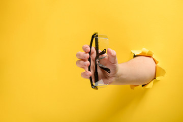 Hand giving safety glasses