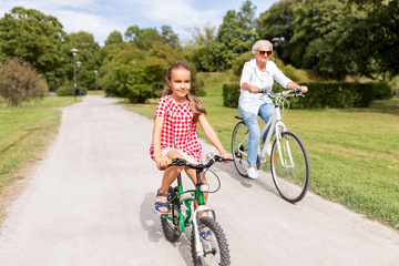 family, leisure and people concept - happy grandmother and granddaughter riding bicycles at summer park