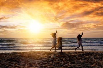 Mutter und ihre Kinder haben Spaß am Strand bei Sonnenuntergang während ihres Sommer Urlaubes