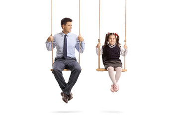 Father and daughter sitting on swings