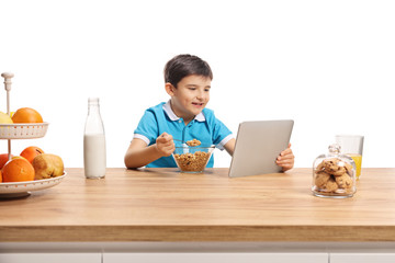 Little boy eating cereals for brekfast at a wooden counter and watching in a tablet